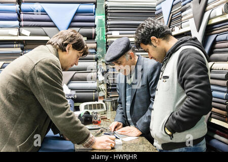 Salesmen and customer surrounded by bolts of wool cloth at fabric stall in the Tehran Bazaar - Stock Photo