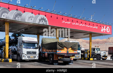 Heavy trucks at Iranian gasoline station on the road to Isfahan. One driver is at a gasoline pump - Stock Photo