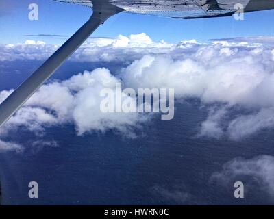 View from window of a light plane flying above the clouds over the ocean. - Stock Photo