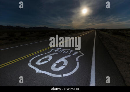 Route 66 sign with full moon in the California Mojave desert. - Stock Photo