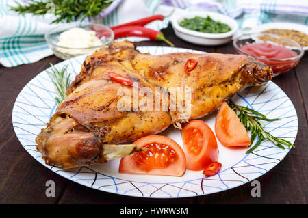 Baked rabbit legs on a plate and different sauces for meat on a dark wooden background. - Stock Photo