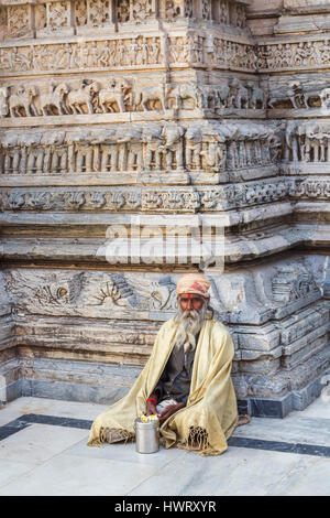 Sadhu sitting cross-legged by a typical carved wall in the Jagdish Temple, a Hindu temple in Udaipur, Indian state - Stock Photo
