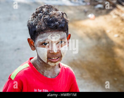 Local smiling young Burmese boy with typical patterned thanaka sunscreen on his face, Dala Township, Yangon (Rangoon), - Stock Photo
