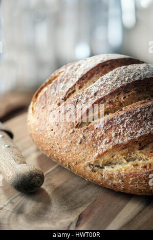Fresh crusty Loaf of bread on wooden table - Stock Photo