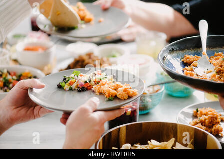 Cropped image of friends having food at dining table in party - Stock Photo
