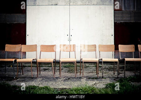 Empty chairs on footpath against closed door - Stock Photo