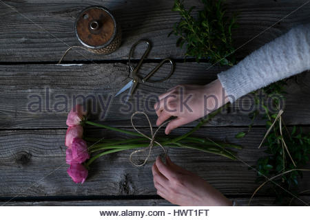Cropped hands of woman tying pink roses with string on wooden table - Stock Photo