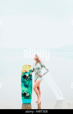 Woman wearing veil holding surfboard while standing at beach against sky during foggy weather - Stock Photo