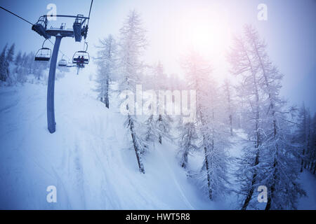 View from chairlift on snowy trees at sunny day - Stock Photo