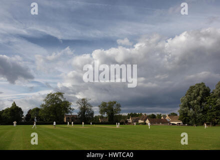 Sunday afternoon village cricket on the green in a Wiltshire village under a dramatic evening summer sky. - Stock Photo