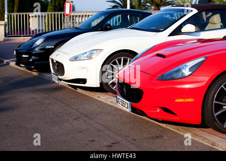 A red Ferrari, a white Maserati and a black Porsche motor car parked next to each other in a side street near the - Stock Photo