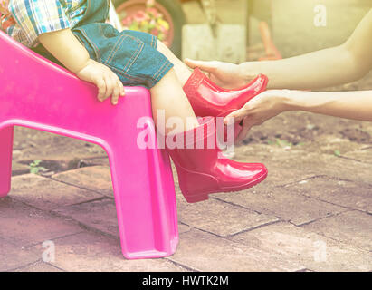 Mother wearing red color boots to baby, Family scene mother and baby - Stock Photo