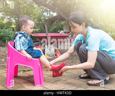 Mother wearing red color boots to baby and talking together  , Family scene mother and baby in  Thailand - Stock Photo