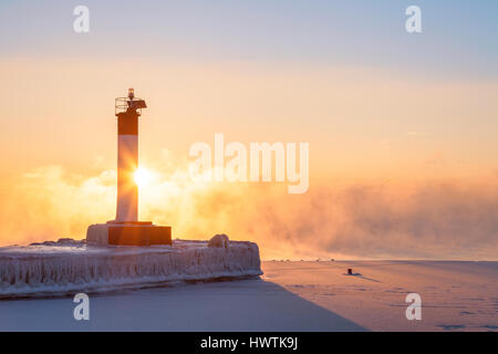 A lighthouse at sunrise on a pier on a very cold winter morning with heavy lake fog. Oakvile, Ontario, Canada. - Stock Photo