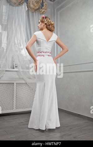 Elegant, beautiful, fashionable woman blonde in a long white dre - Stock Photo