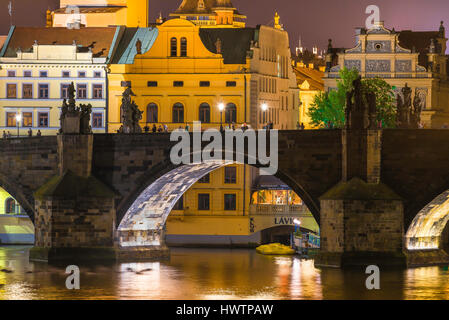 Charles Bridge Prague night, tourists linger on the Charles Bridge at night, seen against the historical old town - Stock Photo