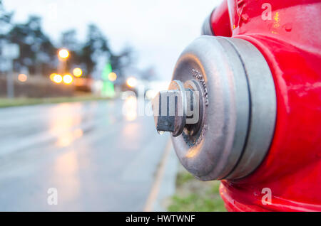 Water drop on red hydrant in the street - Stock Photo
