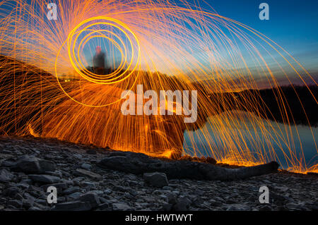 A person standing on a rock against a lake at dusk spinning steel wool on fire with sparks flying in all directions. - Stock Photo