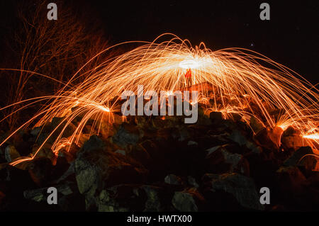 A person standing high on a hill spinning steel wool on fire with sparks bouncing off the rocks toward the camera - Stock Photo