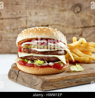 fresh tasty burger and potatoes on wooden cutting board - Stock Photo