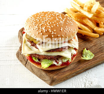 fresh tasty burger on wooden cutting board, top view - Stock Photo