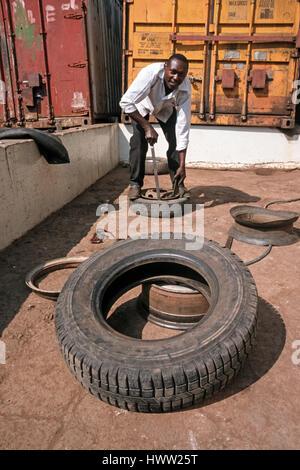 Man repairs a flat car tire at a local repair service, Moshi, Tanzania - Stock Photo