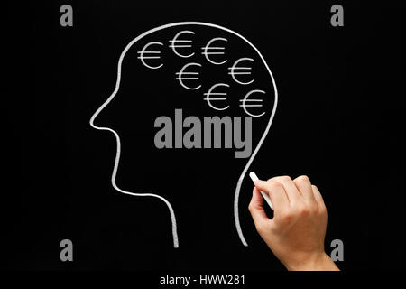 Hand drawing human head and many euro signs with white chalk on blackboard. - Stock Photo