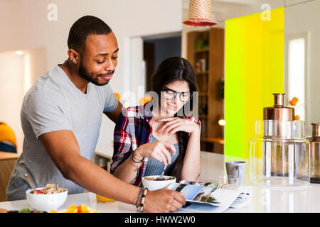 Young couple having breakfast in the kitchen and reading magazine - Stock Photo