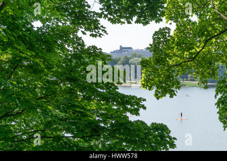 PEOPLE ON STAND UP PADDEL BOARDS ON A LAKE IN HELSINKI SURROUNDED BY TREES - Stock Photo