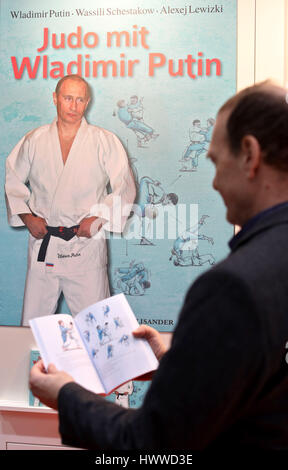 A man leafs through the book 'Judo with Vladimir Putin' at the Leipzig Book Fair in Leipzig, Germany, 23 March 2017. - Stock Photo