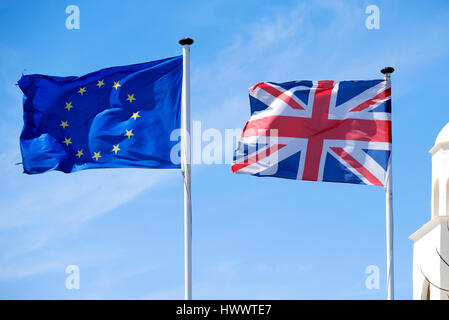 A Union Jack flag flying next a European flag or flag of Europe. Both blowing fiercely in a strong breeze against - Stock Photo
