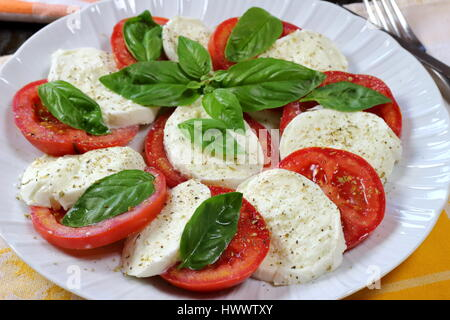 Tomato and buffalo mozzarella Caprese summer salad close up with fork in background and fresh basil on top - Italian - Stock Photo