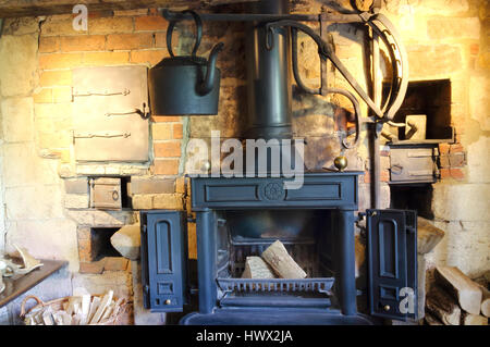 Old style iron, wood burning fireplace with a black hanging kettle - Stock Photo