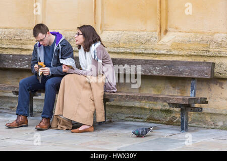 Cirencester - Young couple sitting on bench eating lunch with pigeon on the ground at Cirencester, Gloucestershire - Stock Photo