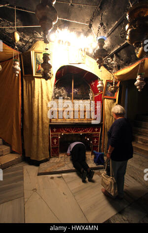Women pray at the silver star marks the traditional site of Jesus' birth in a grotto underneath Bethlehem's Church - Stock Photo