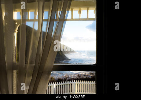 Light falls through soft translucent curtains at the Heceta Head Light bed and breakfast in Yachats, Oregon. - Stock Photo
