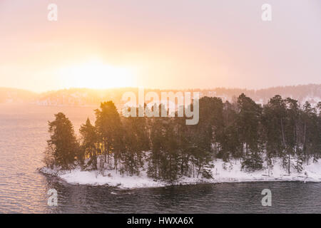 Wintery in Sweden and an island is the Stockholm Archipelago as seen from a ferry boat. - Stock Photo