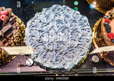 Lavender rose piped frosting iced large cake on display in bakery - Stock Photo