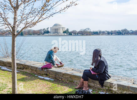 Washington DC, USA - March 17, 2017: Young girls sitting on edge looking over Tidal Basin and Thomas Jefferson Memorial - Stock Photo