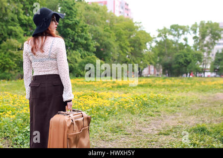 woman in retro dress outdoor suitcase park - Stock Photo