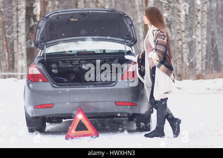 girl wrapped in a blanket placed near the broken car - Stock Photo