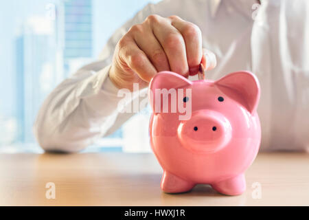 Man putting a coin into a pink piggy bank concept for savings and finance - Stock Photo