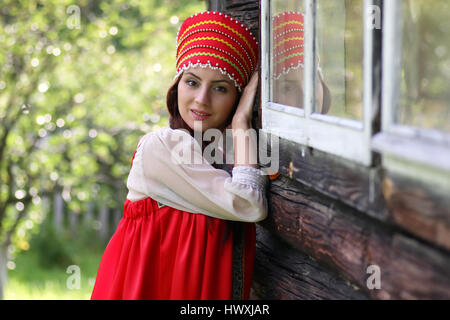Slav woman in traditional dress wooden wall - Stock Photo