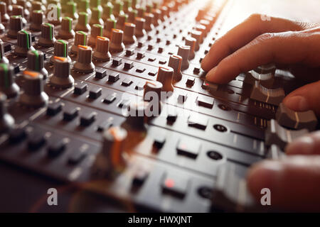 Sound recording studio mixing desk with engineer or music producer - Stock Photo