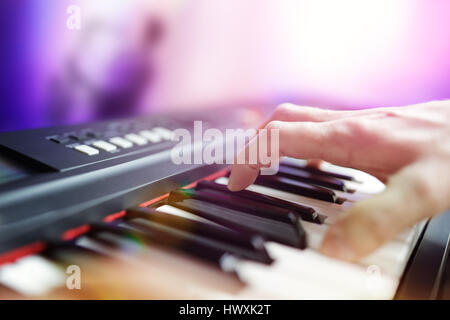 Pianist musician performing live playing keyboard in a band with saxophone player in background - Stock Photo