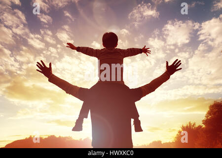 Family time father and son watch and praise the sunset - Stock Photo