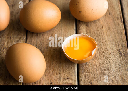 Fresh organic brown eggs scattered on wood table, open yolk, minimalistic, Easter baking concept, closeup - Stock Photo