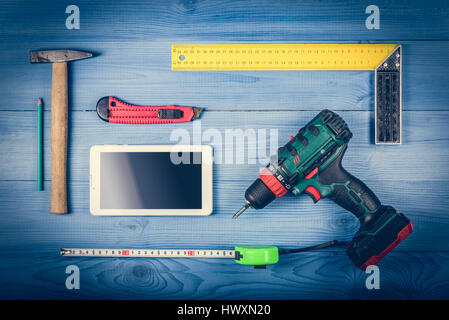Tinker toools on the green wooden surface, and tablet to display web site. DIY concept. - Stock Photo