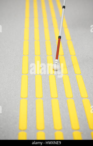 Blind pedestrian walking and detecting markings on tactile paving with textured ground surface indicators for blind and visually impaired. Blindness a