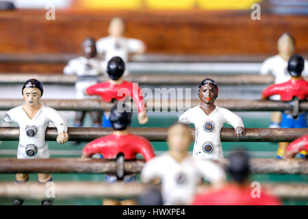An old fussball, foosball or table football game which has painted shite and black players in red and white football - Stock Photo